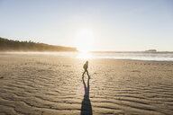 Woman strolling on Long Beach at sunrise, Pacific Rim National Park, Vancouver Island, British Columbia, Canada - CUF04098