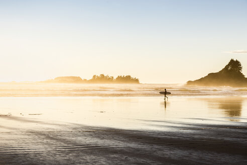 Male surfer carrying surfboard on Long Beach, Pacific Rim National Park, Vancouver Island, British Columbia, Canada - CUF04101