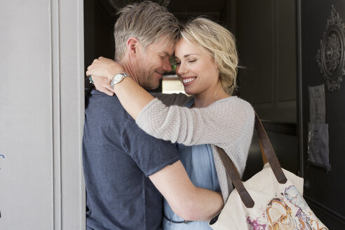 Couple hugging face to face in doorway - CUF04167