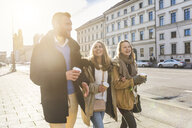 Young man and female friends strolling with takeaway coffee  on city street - CUF04179