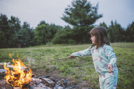 Young girl toasting marshmallow in fire - ISF00920