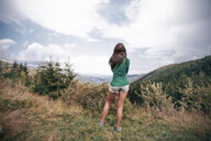 Young woman looking out over mountains, Draja, Vaslui, Romania, rear view - ISF00923