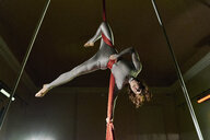 Young female aerial acrobat wrapped upside down in silk rope - CUF04388