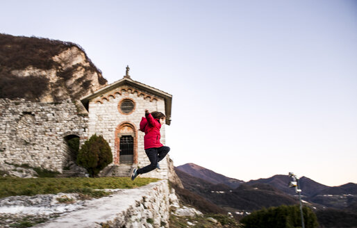 Boy jumping from high wall in mountain landscape, Italy - CUF04394