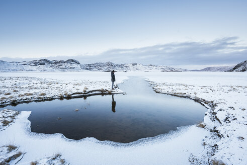 Man standing at water's edge, looking at view, Kleifarvatn, Iceland - CUF04415