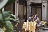 Young couple sitting outside cafe, Turin, Piedmont, Italy - CUF04427