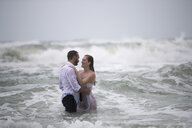 Couple in embrace in sea - ISF00940