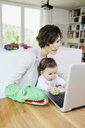 Mother using laptop with baby girl sitting on her lap - ISF01033