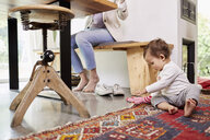 Mother working at kitchen table, whilst baby girl plays on floor. low section - ISF01036