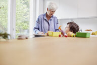 Grandmother and grandson preparing food in kitchen - ISF01045