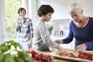 Grandmother and grandson making pizza in kitchen, mother in background using smartphone - ISF01054