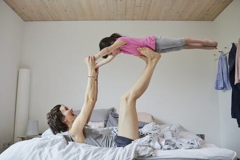 Mother and daughter playing in bedroom, mother balancing daughter on feet - ISF01063