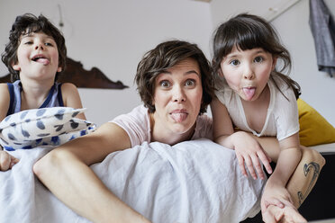 Portrait of mother, son and daughter, lying on bed, poking tongue out - ISF01078