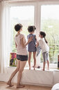 Mother, son and daughter at home, looking out of window, rear view - ISF01108