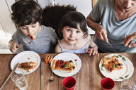 Grandmother sitting at kitchen table with grandchildren, eating pizza, elevated view - ISF01114