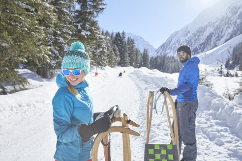 Couple with sledges standing in snow-covered landscape - CVF00474