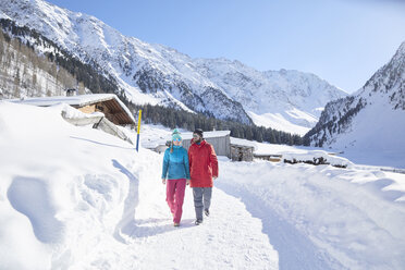 Couple walking in snow-covered landscape - CVF00480