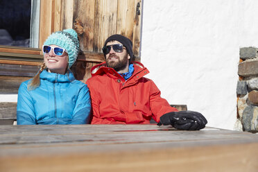 Couple sunbathing in winter at wooden mountain hut - CVF00483