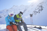 Austria, Tyrol, Kuehtai, two skiers in winter landscape having a break - CVF00501