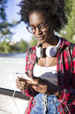 Portrait of young woman with headphones using cell phone - JSRF00046