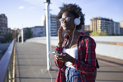 Portrait of young woman on a bridge listening music with headphones - JSRF00049