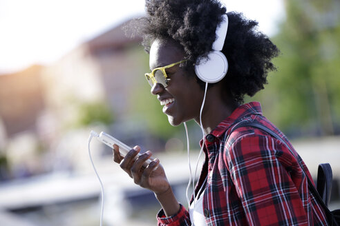 Portrait of laughing young woman using headphones and cell phone - JSRF00052