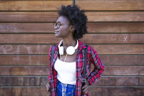 Young woman with backpack and headphones waiting in front of wooden wall - JSRF00058