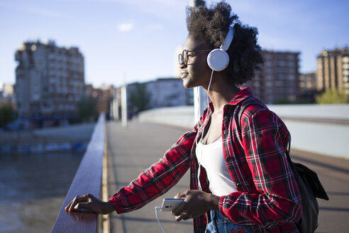 Young woman on a bridge listening music with headphones - JSRF00070