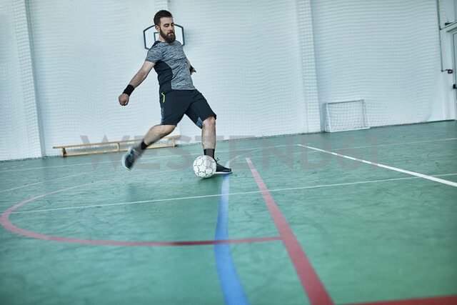 Man playing indoor soccer shooting the ball - ZEDF01409