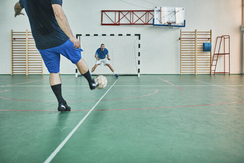 Two men playing indoor soccer shooting at goal - ZEDF01412