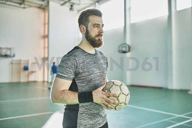 Portrait of indoor soccer player holding the ball - ZEDF01418