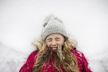 Girl lying on back in snow with eyes closed - CUF04536