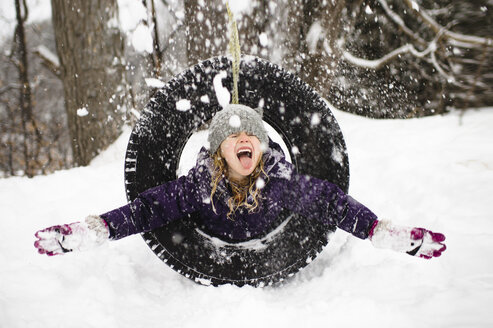 Girl playing in snow on tire swing - CUF04563