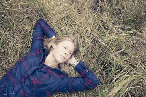Overhead view of young woman lying in long grass - CUF04569