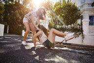 Teenage girl catching friend falling off skateboard, Cape Town, South Africa - CUF04680
