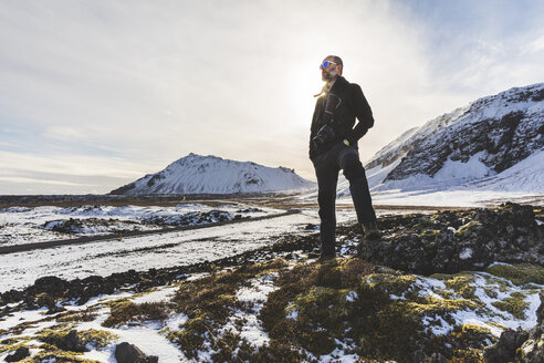 Man standing, looking at view, low angle view, Arnarstapi. Iceland - CUF04725