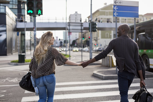 Rear view of young couple holding hands on city pedestrian crossing - CUF04731