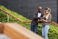 Young businessman and woman looking at digital tablet on city stairway - CUF04734