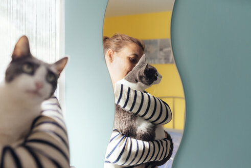 Woman holding a gray cat next to a mirror at home - GEMF01971