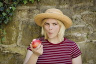 Portrait of young blonde woman with sun hat eating apple - FLLF00039