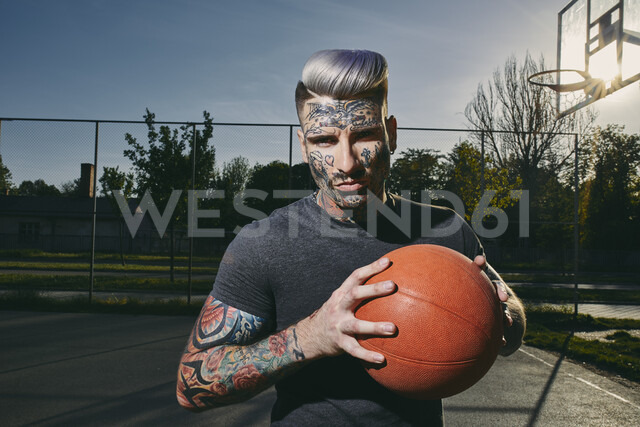 Portrait of tattooed young man with basketball on court - ZEDF01430 - Zeljko Dangubic/Westend61