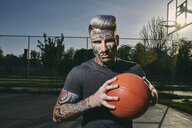 Portrait of tattooed young man with basketball on court - ZEDF01430