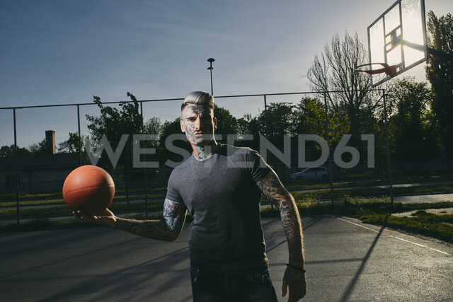 Portrait of tattooed young man with basketball on court - ZEDF01433