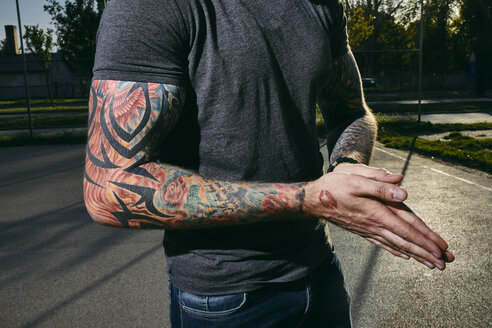 Tattooed arms of a young man outdoors - ZEDF01436