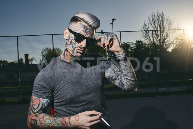 Portrait of tattooed young man wearing sunglasses smoking a cigarette - ZEDF01442 - Zeljko Dangubic/Westend61
