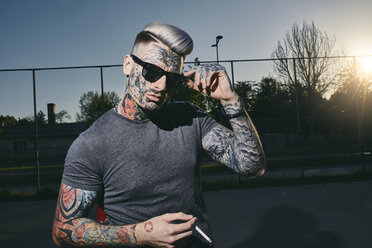 Portrait of tattooed young man wearing sunglasses smoking a cigarette - ZEDF01442