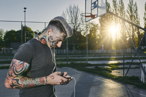 Tattooed young man with smartphone and earbuds - ZEDF01445