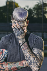 Tattooed young man outdoors hiding his face - ZEDF01448