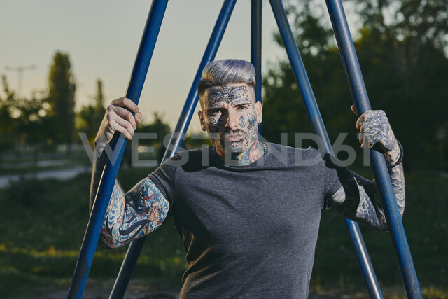 Portrait of tattooed young man outdoors - ZEDF01454