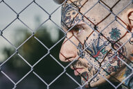 Tattooed face of young man behind fence - ZEDF01457